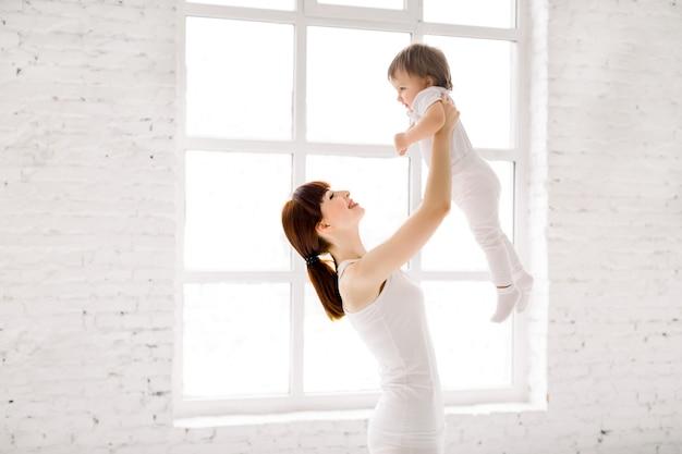 Szczęśliwa powabna sportowa matka w białej odzieży trzyma ślicznej małej dziewczynki up nad głową