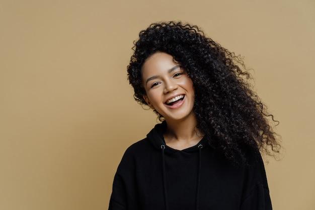 Szczęśliwa pozytywna amerykanin afrykańskiego pochodzenia kobieta z kędzierzawymi włosami przechyla głowę i uśmiecha się szeroko