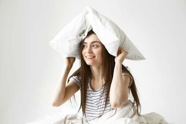 Szczęśliwa pozytywna ciemnowłosa młoda kobieta w pasiastej piżamie odwracająca wzrok z figlarnym uśmiechem podczas zabawy w łóżku, zakrywająca głowę białą poduszką
