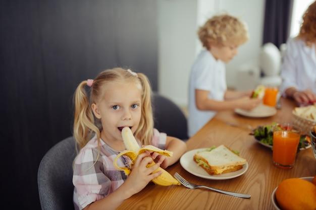 Szczęśliwa pozytywna dziewczyna gryzie pysznego banana
