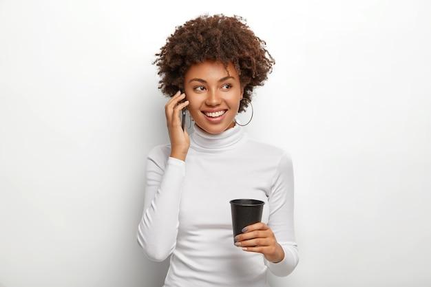 Szczęśliwa pozytywna dziewczyna z fryzurą afro dobrze czuje się podczas ożywionej komunikacji