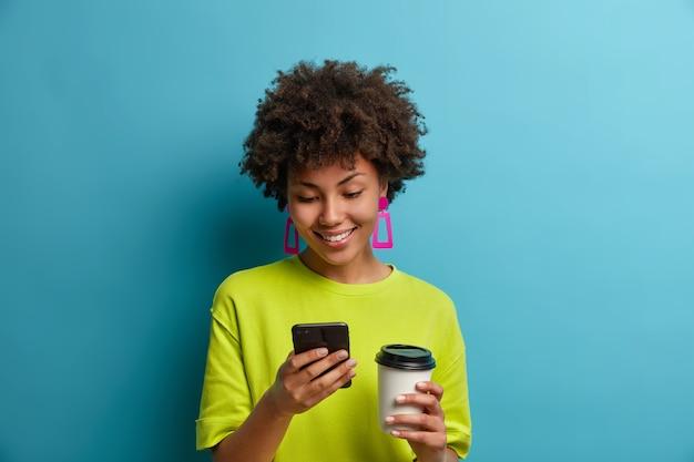 Szczęśliwa pozytywna, etniczna młoda kobieta pisze wiadomości lub wybiera numer telefonu na telefon, pije kawę na wynos, korzysta z aplikacji mobilnej online, przeszukuje sieć, czyta blogi i czaty w sieciach społecznościowych