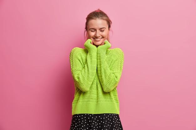 Szczęśliwa pozytywna kaukaska dziewczyna trzyma obie ręce pod brodą, radośnie się uśmiecha, wyraża szczere emocje, stoi z zamkniętymi oczami, odbiera komplementy, ubrana w za duży sweter