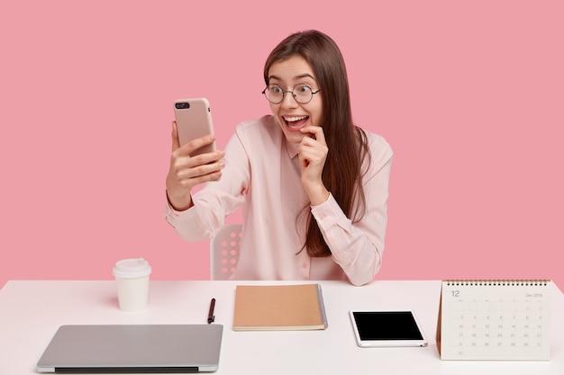 Szczęśliwa pozytywna kobieta trzyma telefon komórkowy przed twarzą, nawiązuje połączenie wideo, jest podłączona do bezprzewodowego internetu, nosi formalną koszulę