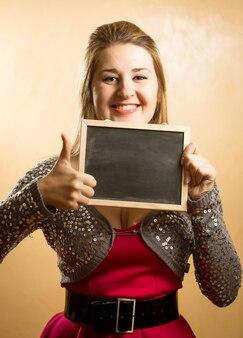 Szczęśliwa pozytywna kobieta trzymająca tablicę i kciuk w górę