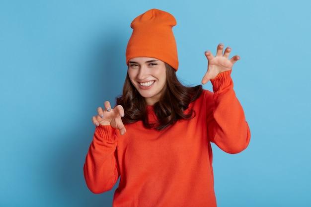 Szczęśliwa pozytywna kobieta ubrana na co dzień pomarańczowy sweter i kapelusz pokazujący gest pazurów i patrząc bezpośrednio na aparat z uśmiechem, pozowanie na białym tle nad niebieską ścianą.