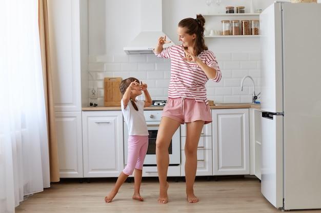 Szczęśliwa pozytywna kobieta ubrana w pasiastą koszulę tańcząca z córką w domu, wykonująca ruch gestem zwycięstwa, patrząca na siebie z szczęśliwym uśmiechem, wspólna zabawa w kuchni.