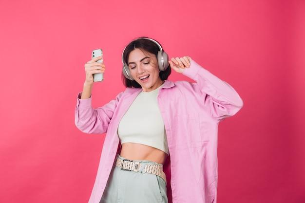 Szczęśliwa pozytywna kobieta w słuchawkach na różowej czerwonej ścianie
