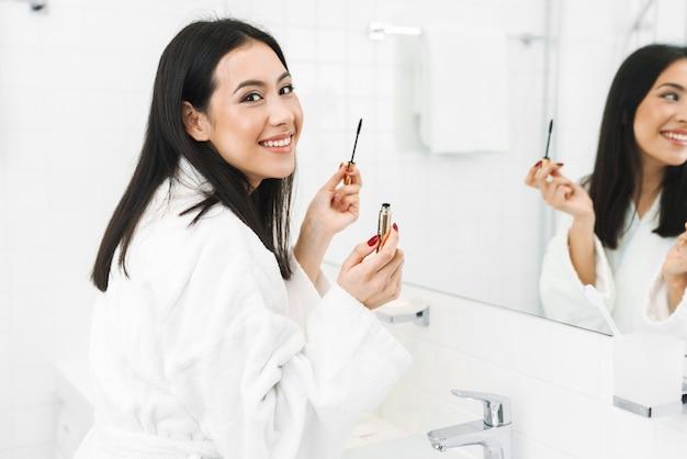 Szczęśliwa pozytywna młoda kobieta w domu w domu w łazience stosuje makijaż.