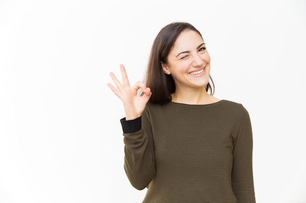 Szczęśliwa pozytywna piękna kobieta robi zadowalającemu ręka gestowi