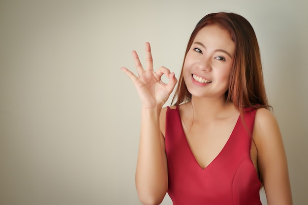 Szczęśliwa pozytywna, pomyślna akceptująca kobieta pokazująca ok gest ręki, azjatycka modelka