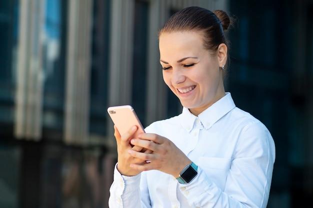 Szczęśliwa pozytywna rozochocona biznesowa kobieta, młoda piękna dziewczyna patrzeje smartphone