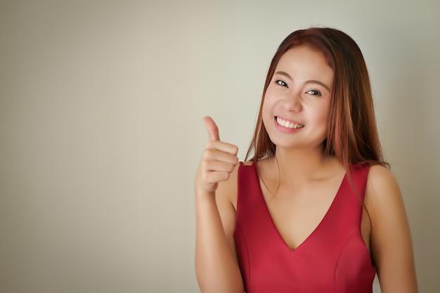 Szczęśliwa pozytywna udana akceptująca kobieta pokazująca kciuk w górę gest, azjatycka modelka