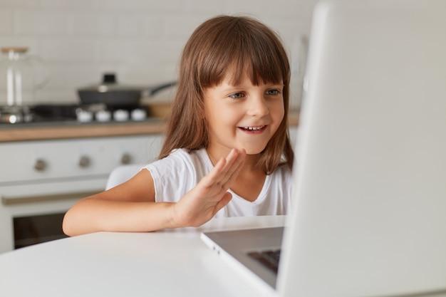 Szczęśliwa pozytywna uśmiechnięta kobieta o ciemnych włosach siedzi w kuchni przed laptopem, prowadzi rozmowę wideo lub transmituje transmisję na żywo na swoim blogu dla dzieci.
