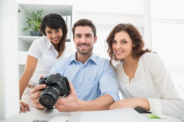 Szczęśliwa praca zespołowa pozuje z cyfrową kamerą