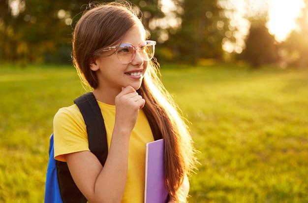 Szczęśliwa preteen dziewczyna w okularach ze szkolnym plecakiem i zeszytami uśmiechnięta i odwracająca wzrok, stojąc na zielonej łące w słonecznym parku