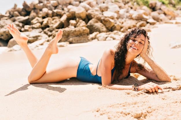 Szczęśliwa przyjemna kobieta ubrana w niebieski kostium kąpielowy relaksuje się na piaszczystej plaży