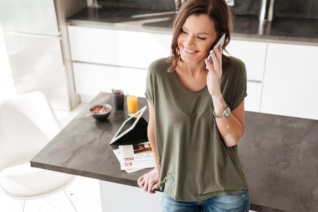 Szczęśliwa przypadkowa kobieta opowiada na telefonie komórkowym