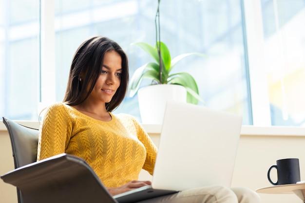 Szczęśliwa przypadkowa kobieta siedzi na krześle biurowym z laptopem w biurze