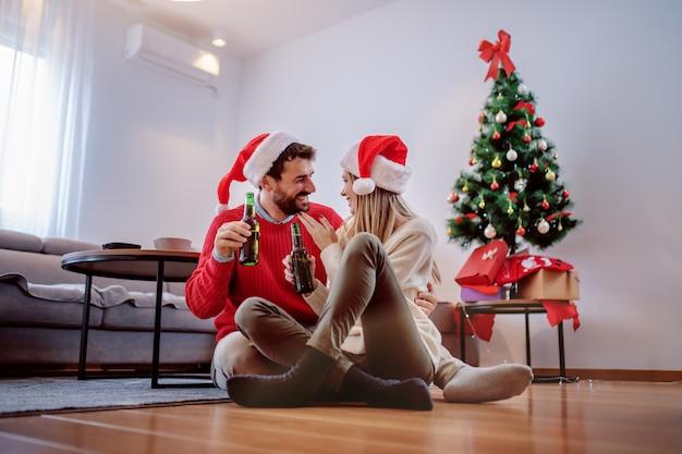 Szczęśliwa przystojna caucasian para z santa kapeluszami na głowach siedzi na podłoga z piwną butelką w rękach i cuddling. w tle jest choinka z prezentami pod nią. wnętrze salonu.