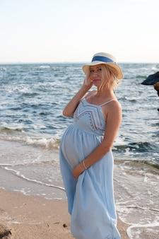 Szczęśliwa przyszła matka pozuje w pobliżu oceanu w niebieskiej sukience w stylu prowansalskim i kapeluszu, backlite