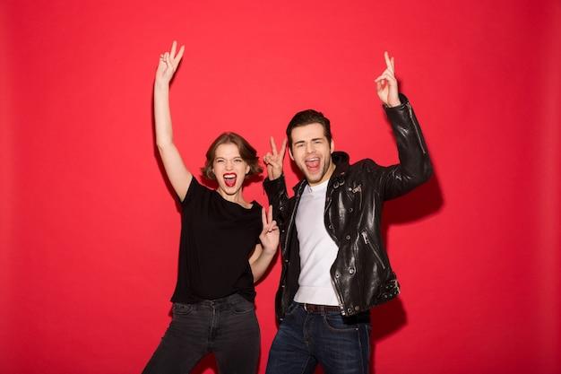 Szczęśliwa punkowa para pokazuje pokojów gesty i patrzeje