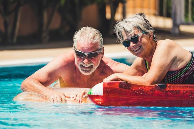 Szczęśliwa radość wesoła para dorosłych seniorów bawi się w basenie z modnym kolorowym materacem lilos na błękitnej wodzie w hotelowym kurorcie na letni wypoczynek styl życia