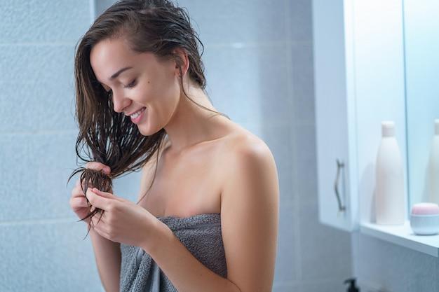 Szczęśliwa radosna brunetka kobieta w ręcznik kąpielowy stosuje odżywkę do włosów w łazience po prysznicem w domu