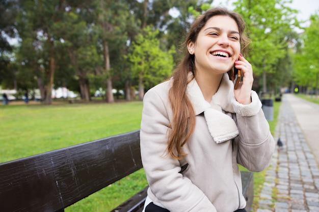 Szczęśliwa radosna dziewczyna cieszy się śmiesznego telefon