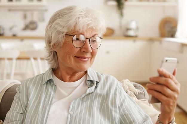 Szczęśliwa radosna emerytka w okrągłych okularach surfuje po internecie na telefonie komórkowym, patrzy na ekran telefonu komórkowego z szerokim uśmiechem, rezerwuje bilety lotnicze, planuje podróż lub przewija zdjęcia za pośrednictwem sieci społecznościowej