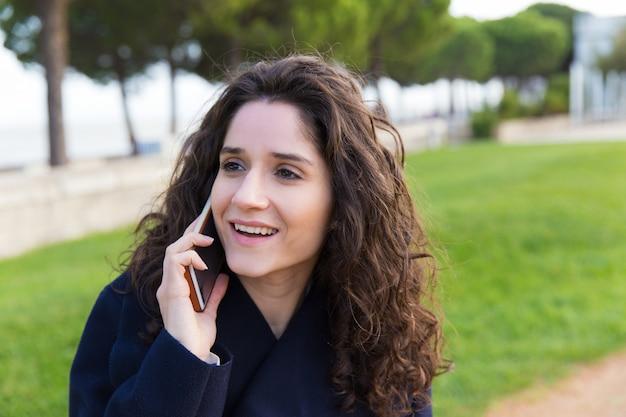 Szczęśliwa radosna kobieta opowiada na telefonie komórkowym