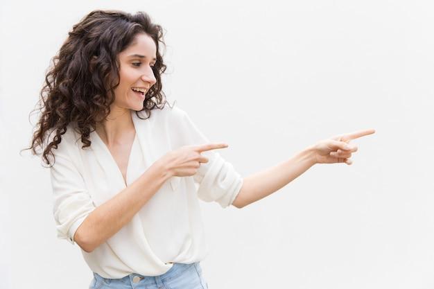 Szczęśliwa radosna kobieta patrzeje daleko od i wskazuje