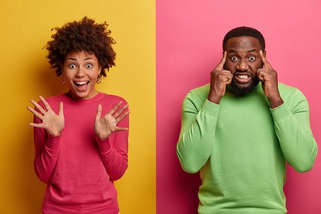 Szczęśliwa radosna kobieta unosi dłonie, macha dłońmi na cześć, wykonuje przyjazny gest, intensywnie brodaty mężczyzna dotyka skroni, próbuje się skoncentrować, zaciska zęby, ma ból głowy, stoi pod dwoma kolorowymi ścianami