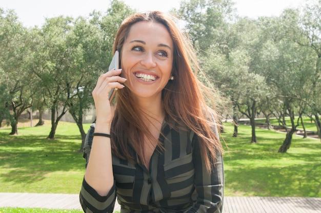 Szczęśliwa radosna młoda kobieta gawędzi na komórce na zewnątrz