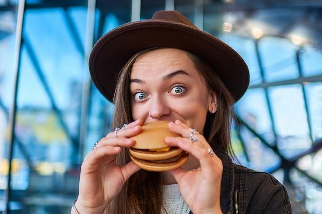 Szczęśliwa radosna modna modna głodna kobieta z zdziwionymi szerokimi oczami je hamburger w restauraci fast food