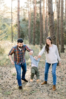 Szczęśliwa radosna rodzina, przystojny brodaty ojciec, ładna brunetka matka i uroczy słodki synek, trzymając się za ręce i spacerując w jesiennym sosnowym lesie z sosnami