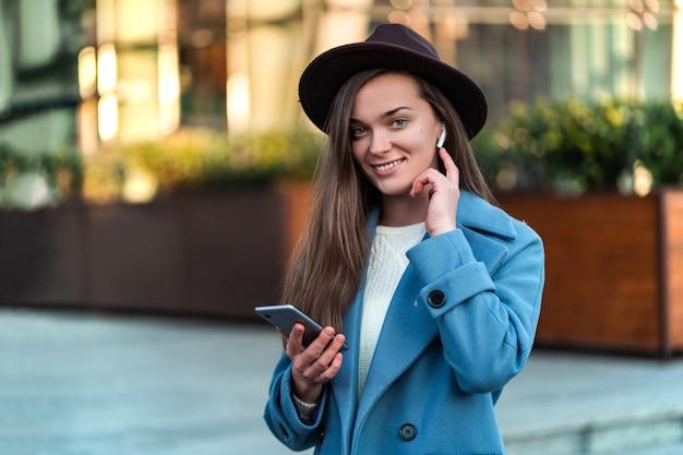 Szczęśliwa radosna stylowa modna brunetka hipster kobieta w kapeluszu i niebieskim płaszczu z bezprzewodowymi białymi słuchawkami cieszy się i słucha muzyki w centrum miasta. współczesny styl życia i technologia
