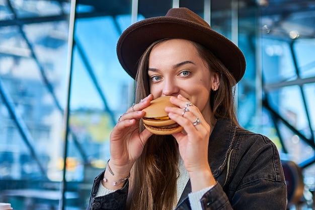 Szczęśliwa radosna stylowa modna przypadkowa nowożytna głodna kobieta je hamburger w restauraci fast food