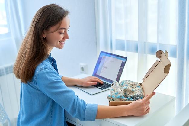 Szczęśliwa radosna zadowolona przypadkowa młoda atrakcyjna uśmiechnięta kobieta otrzymała paczkę z ubraniami ze sklepu internetowego po zakupach online i zamówieniu towaru