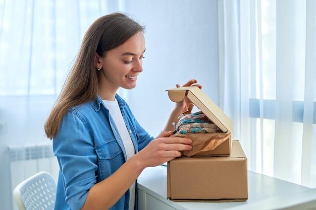 Szczęśliwa radosna zadowolona przypadkowa młoda atrakcyjna uśmiechnięta kobieta otrzymała paczki ze sklepu internetowego