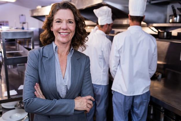Szczęśliwa restauracyjna kierownik pozycja z rękami krzyżował w handlowej kuchni