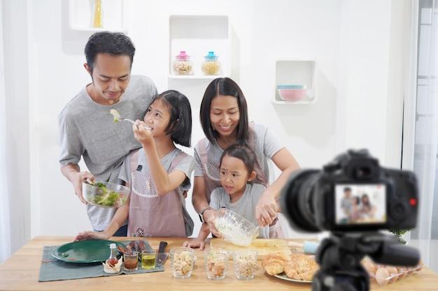 Szczęśliwa rodzina asian robi cyfrowy bloger vlog wideo z gotowaniem w kuchni
