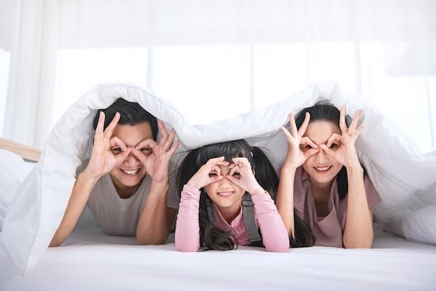 Szczęśliwa rodzina azjatyckich r. na łóżku w sypialni w domu.