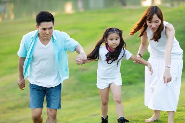 Szczęśliwa rodzina azji bawi się z dziećmi w parku. szczęśliwa rodzina ojciec matka i córka dziecka