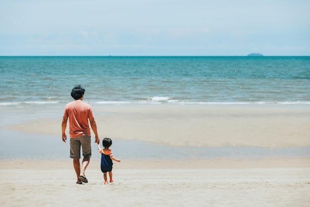Szczęśliwa rodzina azji ojciec i dziecko relaks i wspólne zwiedzanie na plaży w dzień w tajlandii, koncepcja wakacji letnich podróży