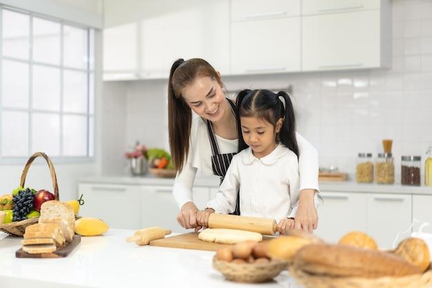 Szczęśliwa rodzina azji z córką robi ciasto przygotowując pieczenie ciasteczek, córka pomaga rodzicowi w przygotowaniu wypieku koncepcja rodziny