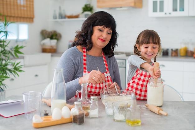 Szczęśliwa rodzina babcia i wnuczka gotują razem. dziewczyna wlewa mąkę z warkoczykami.