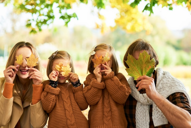 Szczęśliwa rodzina bawi się jesiennymi liśćmi