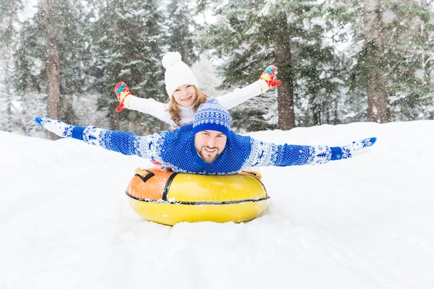 Szczęśliwa rodzina bawi się na świeżym powietrzu dziecko i ojciec bawią się zimą aktywny zdrowy styl życia