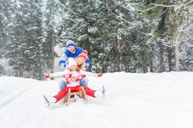 Szczęśliwa rodzina bawi się na świeżym powietrzu dziecko matka i ojciec bawią się zimą zdrowy styl życia